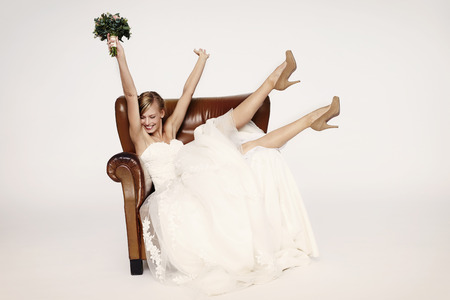 Photo for Excitable bride in armchair, cheering - Royalty Free Image