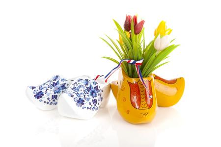 Foto de Pair of typical Dutch wooden shoes with tulips over white background - Imagen libre de derechos