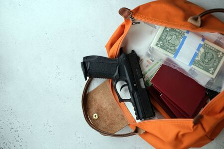 Foto de The gun is on the money with your passport, wallet and ammunition. gun passport money. the concept is to escape from the country to lay low and escape from prosecution after Soberania crimes. - Imagen libre de derechos