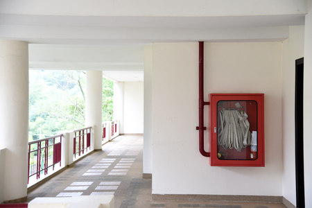 Photo pour Fire extinguisher and fire hose reel in hotel corridor. Fire hoses rack for use. - image libre de droit