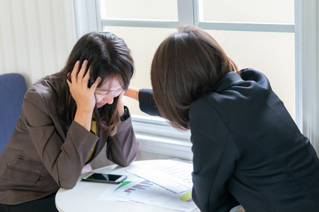 Foto de Business woman consoling her friend that suffering  about problem working - Imagen libre de derechos