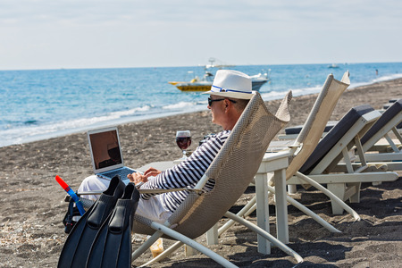 Man working remotely on the computer, sitting on the beach and drinking wine.