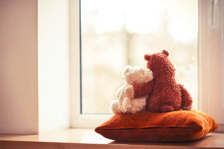 Photo pour Two embracing loving teddy bear toys sitting on window-sill - image libre de droit