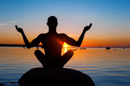 Photo for Meditating man silhouette on vibrant sunset background. Multicolored summertime horizontal outdoors image. View from backside. - Royalty Free Image