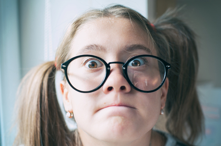 Photo pour Portrait of glad funny surprised girl with ponytails in glasses. Indoors vibrant closeup horizontal image with filter. - image libre de droit