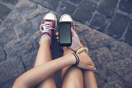 Foto de teenager girl sitting with mobile phone in hand, in ancient stone floor - Imagen libre de derechos