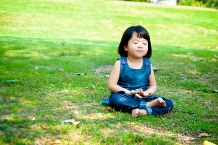 Photo pour Little asian girl practicing mindfulness meditation outdoor in a park. - image libre de droit