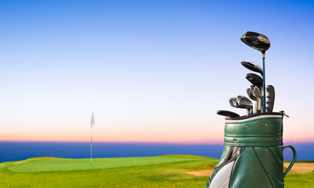 Photo for golf equipment and golf bag on green and hole as background. - Royalty Free Image