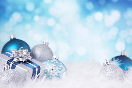 Photo pour Blue and silver Christmas baubles and a gift on a soft feathery surface in front of defocused blue and white lights. - image libre de droit