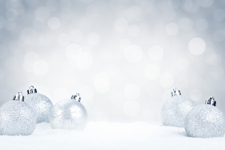 Foto de Silver Christmas baubles on snow with defocused silver and white lights in the background. Shallow depth of field. - Imagen libre de derechos