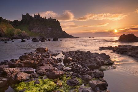 Foto de The ruins of the Dunluce Castle on the Causeway Coast of Northern Ireland. Photographed at sunset. - Imagen libre de derechos
