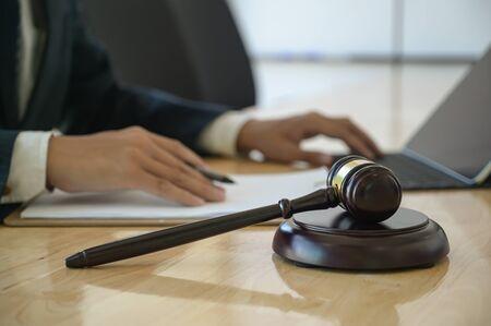 Foto de Concept of justice, Hammer placed on work desk with lawyer uses a laptop sitting behind. - Imagen libre de derechos