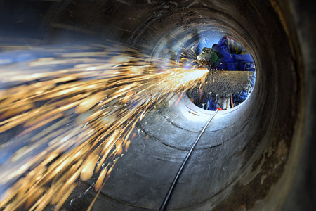 Photo pour Worker during use electric wheel grinding on steel structure in factory and many sharp sparks inside confined space . - image libre de droit