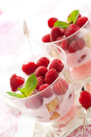 raspberry dessert with cream  and biscuits in glasses