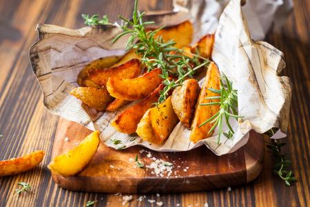 Photo pour Roasted potato wedges with herbs and salt - image libre de droit