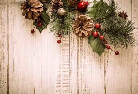 Foto de Christmas background with fir branches,pinecones and berries on the old wooden board - Imagen libre de derechos