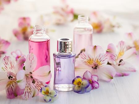 Photo pour Bottles of essential aromatic oils surrounded by fresh flower - image libre de droit
