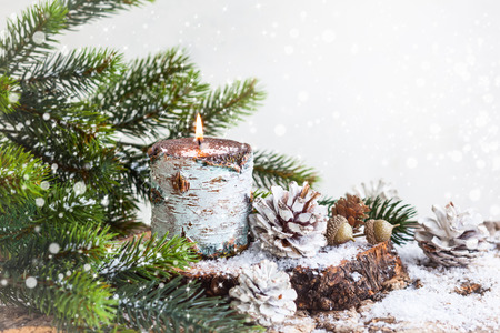 Photo pour Christmas decoration with burning candle,fir branches and pine cones - image libre de droit