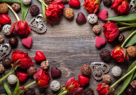 Foto de Gourmet chocolates and red tulips for Valentine's Day - Imagen libre de derechos