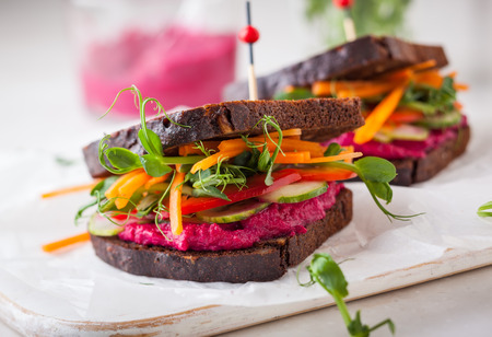 Photo for gluten free vegan sandwiches with beet hummus, raw vegetables and sprouts. soft focus - Royalty Free Image