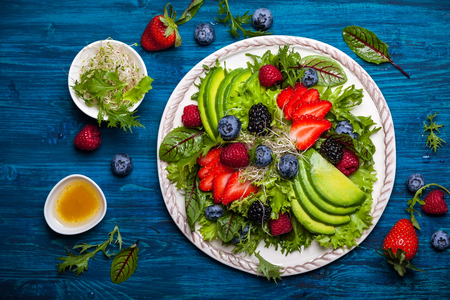Photo pour Mixed salad leaves with berries, avocado and honey-mustard dressing - image libre de droit
