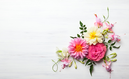 Foto de Festive flower composition on the white wooden background. Overhead view - Imagen libre de derechos