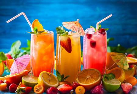 Foto de Different types of summer drinks in glasses, cubes of ice and slice of fruits  on blue table. Healthy vitamin fruit and berry drinks. - Imagen libre de derechos