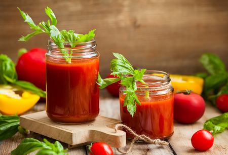 Photo for Spicy tomato drink with celery and pepper. Tomato drink in jar surrounded of fresh vegetables on a wooden table - Royalty Free Image