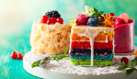 Foto de Various slices of cakes on a white tray: rainbow cake, raspberry cake and almond cake. Sweets decorated with fresh berries and flowers for holiday - Imagen libre de derechos