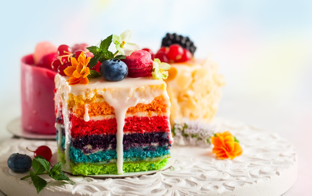 Photo pour Various slices of cakes on a white tray: rainbow cake, raspberry cake and almond cake. Sweets decorated with fresh berries and flowers for holiday - image libre de droit