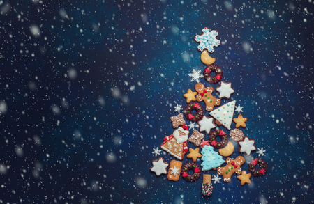 Photo for Assorted Christmas cookies in the shape of a Christmas tree on the blue background. Top view. - Royalty Free Image