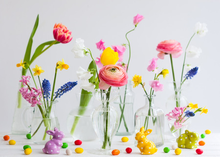 Photo for Beautiful flowers bouquets in glass vases on festive Easter table. Colored Easter eggs in egg cups - Royalty Free Image