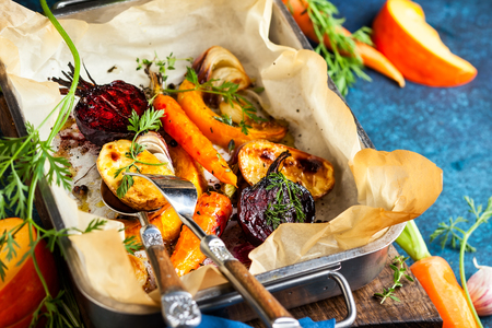 Photo for Oven Roasted vegetables with garlic and herbs on the baking tray. Autumn-winter root vegetables. - Royalty Free Image