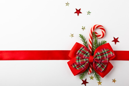 Foto de Christmas red ribbon with bow and candy cone on white background. Top view. Christmas decor for gift box. - Imagen libre de derechos