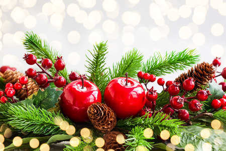 Photo pour Christmas decoration with fir tree, pine cones, red apples and holly berries - image libre de droit