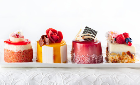 Foto de Various mini cakes on a white plate. Sweets decorated with fresh berries and flowers for holiday. - Imagen libre de derechos