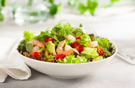 Photo for Fresh summer salad with shrimp, avocado and tomato cherry in bowl on light table. - Royalty Free Image