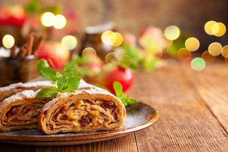 Foto de Traditional pieces of apple strudel with cinnamon,raisin, powdered sugar and mint. Dessert for Christmas. - Imagen libre de derechos