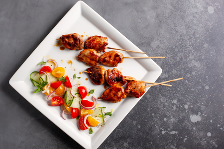 Photo for Delicious grilled meat skewers with summer salad of cherry tomatoes, cucumbers and red onions.Top view with copy space. - Royalty Free Image