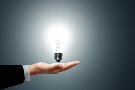 Bulb light in hand on gray background