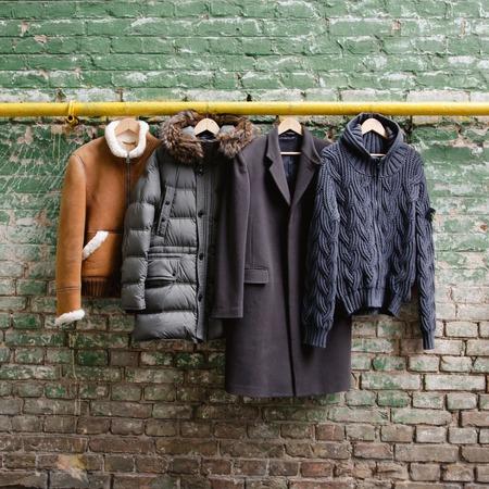 Foto de Men's trendy clothing on hangers on grunge brick wall. Concept background - Imagen libre de derechos