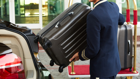 Photo pour Bellboy taking baggage of guest from thee car to his room - image libre de droit