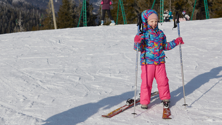 Foto de A happy little girl off skiing with slides - Imagen libre de derechos