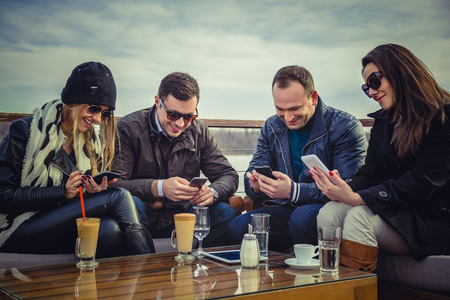 Foto de A group of people looking at a cell phone and laughing - Imagen libre de derechos