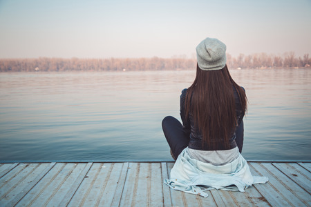 Foto de Girl sitting on pier and lookingat the river - Imagen libre de derechos