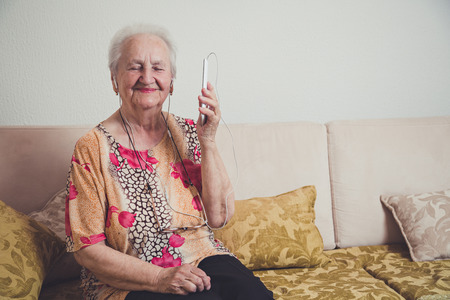 Foto de Senior woman listening music on a mobile phone - Imagen libre de derechos