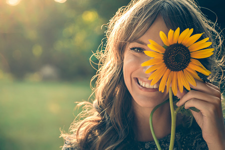 Foto de Girl in park smiling and covering face with sunflower - Imagen libre de derechos