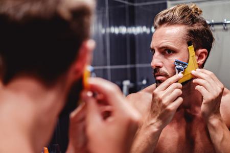 Foto de Hipster man shaving his beard in the bathroom - Imagen libre de derechos
