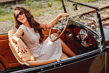 Photo pour Girl laughing while driving old classic car and looking behind her - image libre de droit