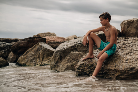 Photo for Boy sitting on the rock with leg in the water and thinking - Royalty Free Image